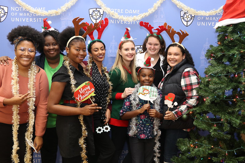 Group photo of female students wearing reindeer headbands next to a Christmas tree