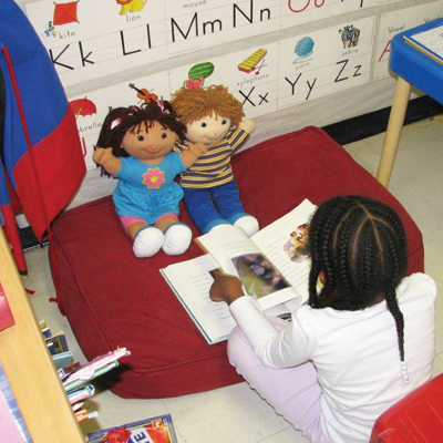 Little girl reading to 2 cabbage patch kids