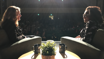 Author and interviewer on lit stage in front of the auditorium