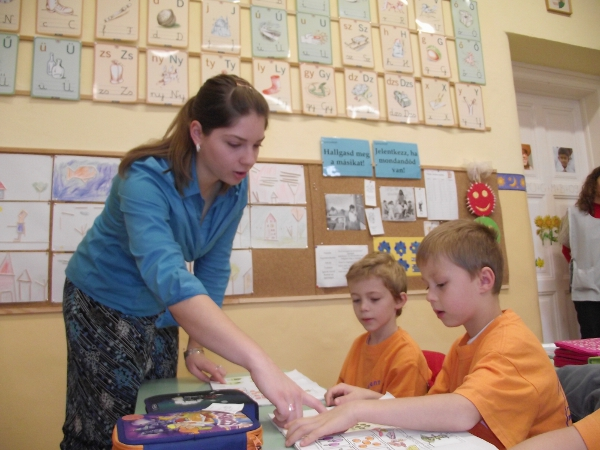 Student teacher with two little boys looking at a book