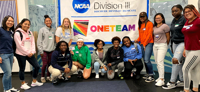 group of student athletes next to NCAA One Team banner