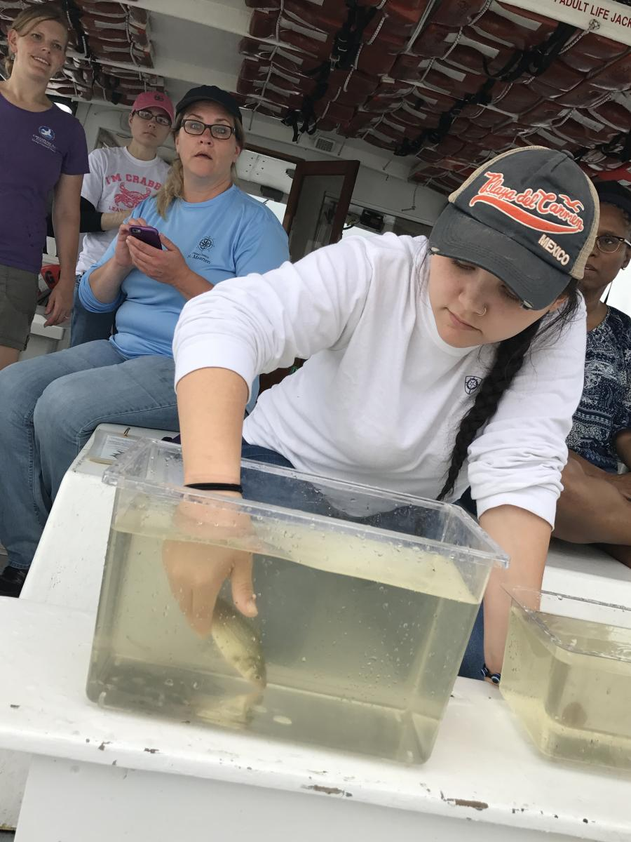 Life on Chesapeake student holds fish