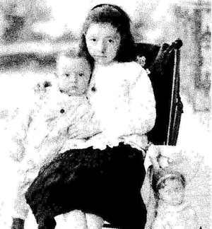 Old photo of a young girl sitting with a baby