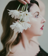 Woman poses holding white flowers next to her head