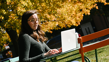 Student outside on campus with a laptop