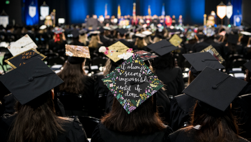 Back of crowd of students wearing graduate caps at commencement