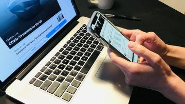 hands hold cell phone in front of laptop