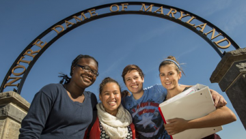 Four female students under the NDMU arch