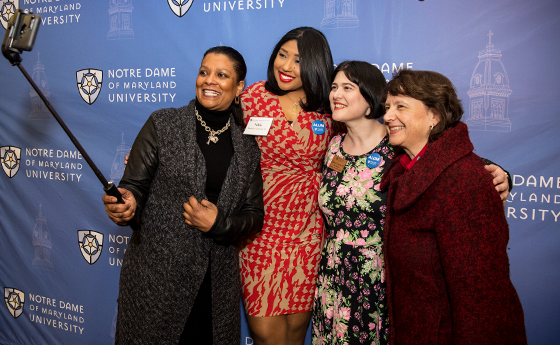 Four women taking a selfie in front of the NDMU step and repeat