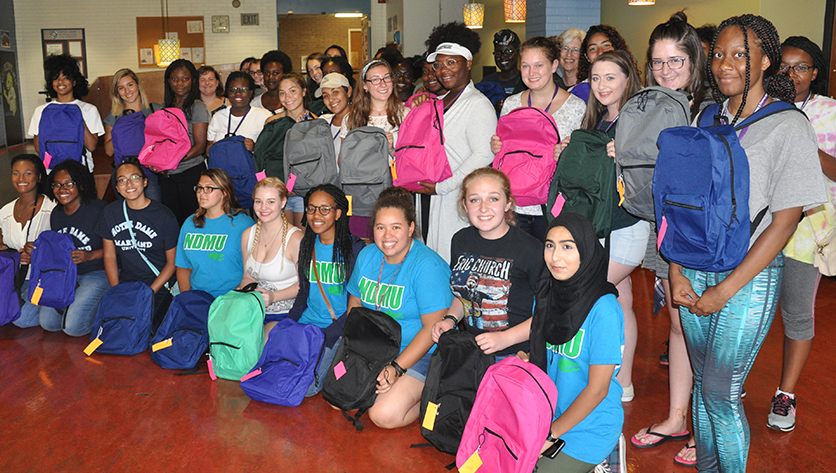 Group photo of students holding backpacks