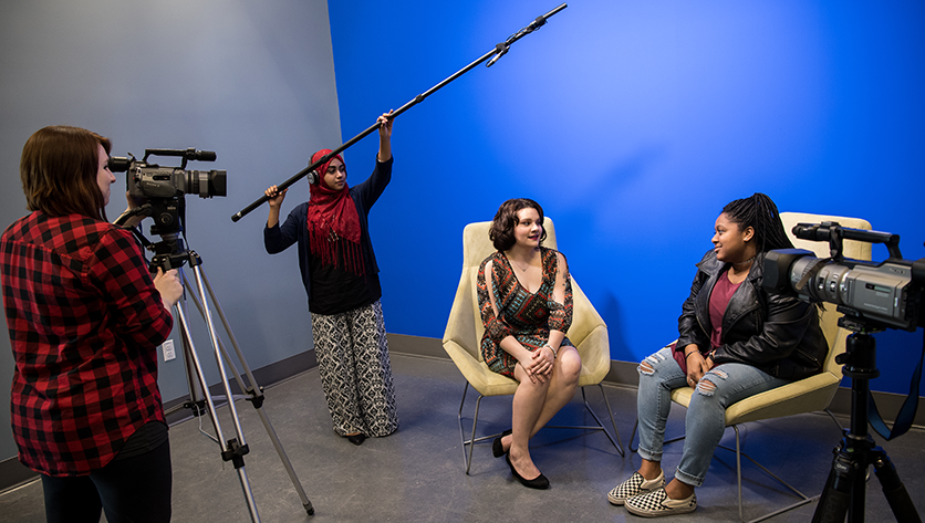 Students in front of the blue screen using the video and audio equipment to record an interview