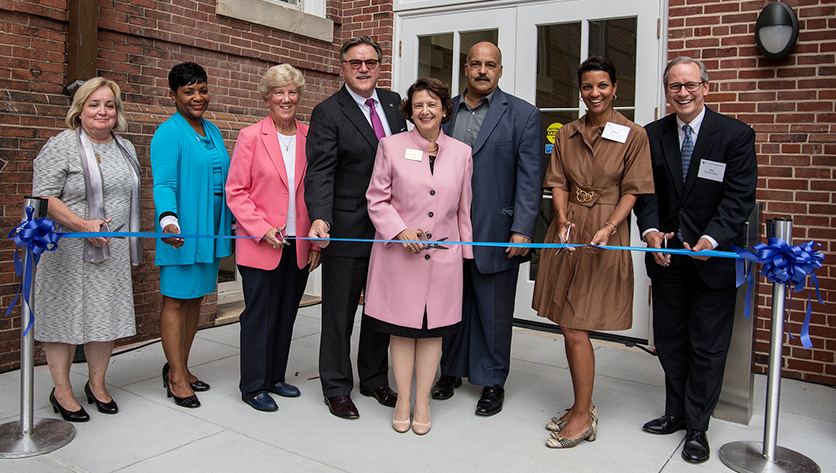 NDMU representatives and distinguished guests cutting the ribbon in front of Gibbons Hall