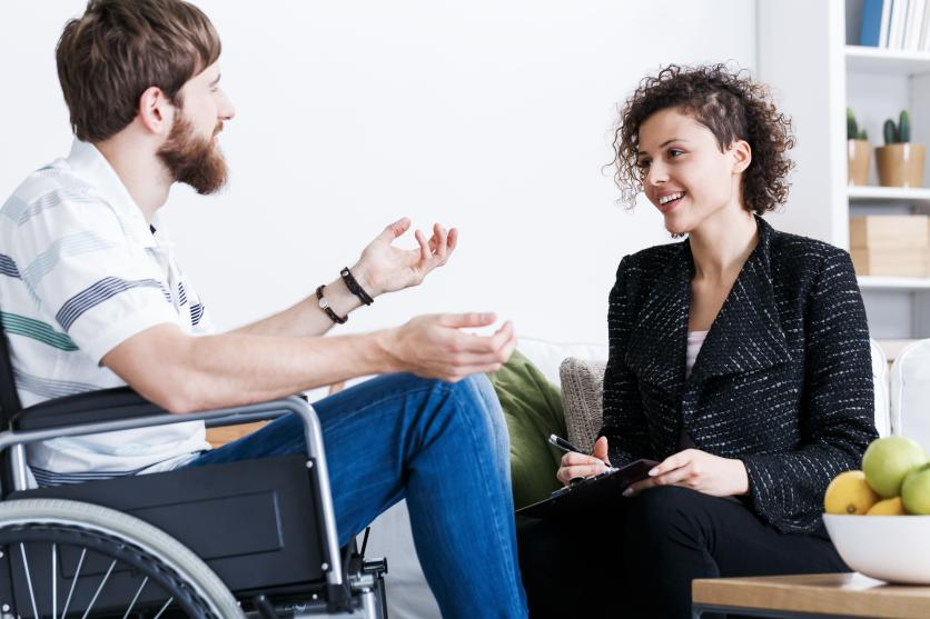 Man in a wheel chair talking to a therapist