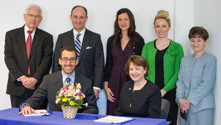 Group photo of administrators signing agreement