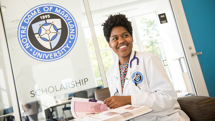 Nursing student sitting in front of NDMU seal