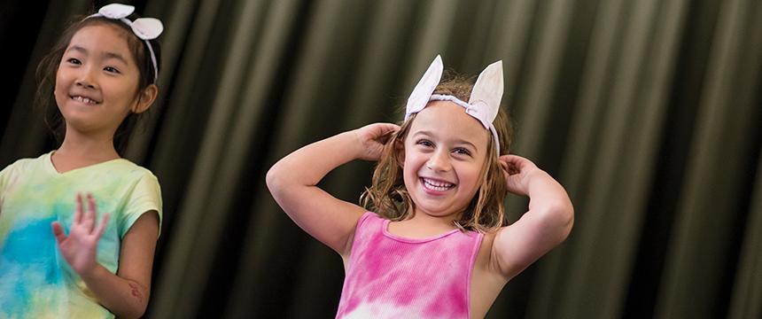 Two little girls on stage wearing bunny ears
