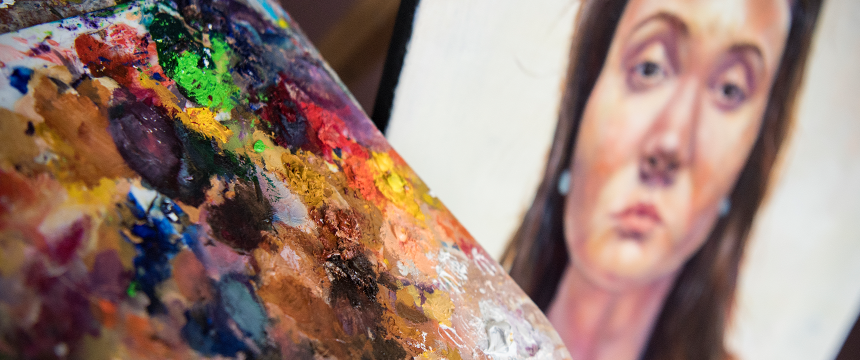 paint palette in the foreground with a painted student portrait of a girl in the background