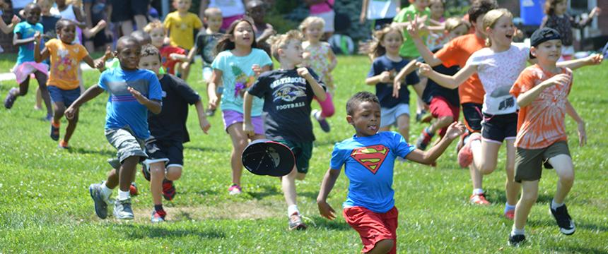 Many kids running across the grass