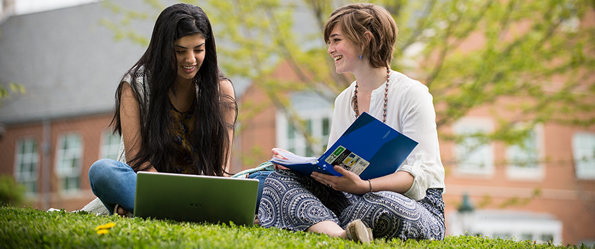 Two girls sitting in the grass looking at books and smiling