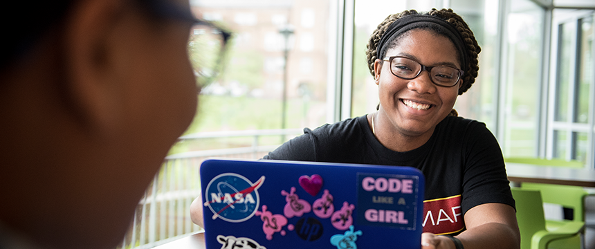 Student at a laptop with stickers such as NASA and Girls who Code