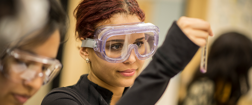 Student wears protective eye goggles and holds a test tube