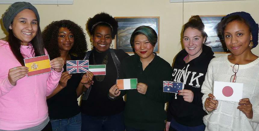 Six smiling students holding flags from different countries