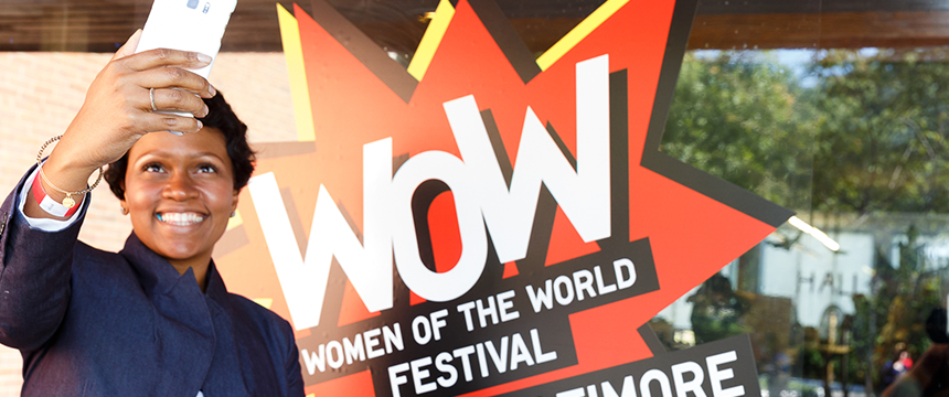 Women taking a selfie next to WOW logo