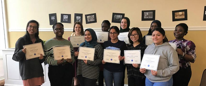 a group of tutors in front of a wall holding certificates
