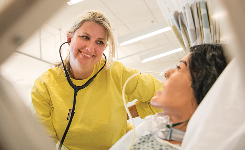 Nursing student wearing stethoscope and looking at SIM patient