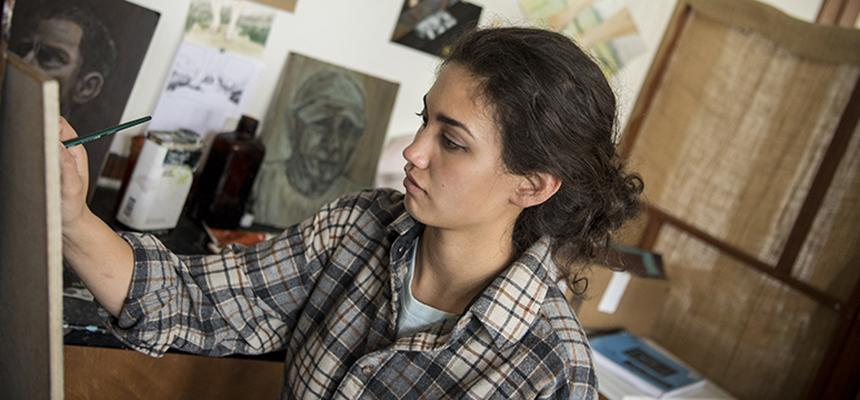 Student sitting at easel painting