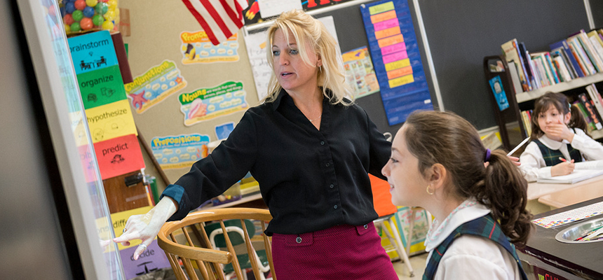 Teacher with a student pointing to the chalkboard