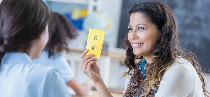 "Teacher holding a flashcard with letter ""g"" up for student"