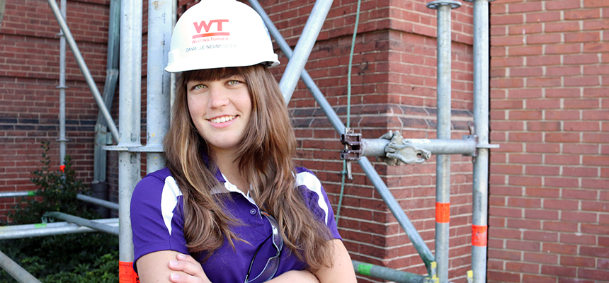 Student wearing a hard hat with scaffolding behind her