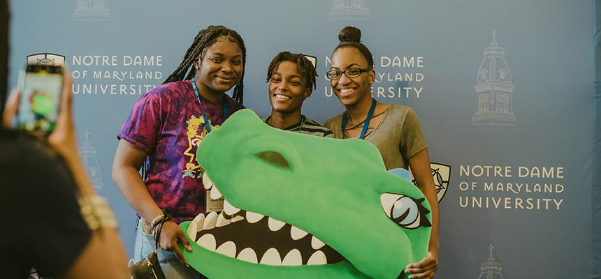 3 students holding a gator poster getting their photo taken