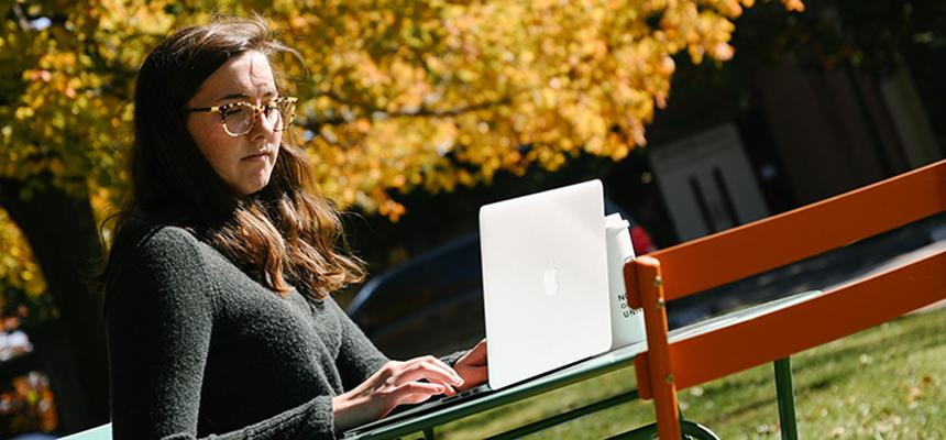 student sitting with laptop outside