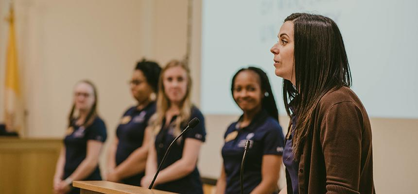 Director presents at a podium with four admissions counselors standing beside her
