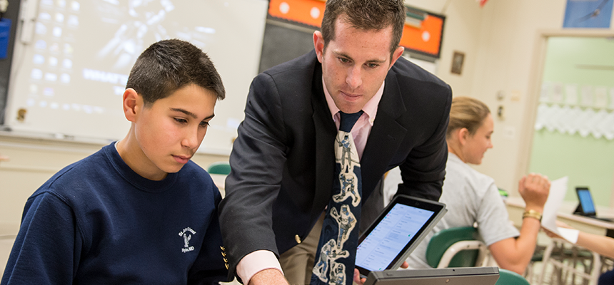 Male teacher assisting a student on a laptop