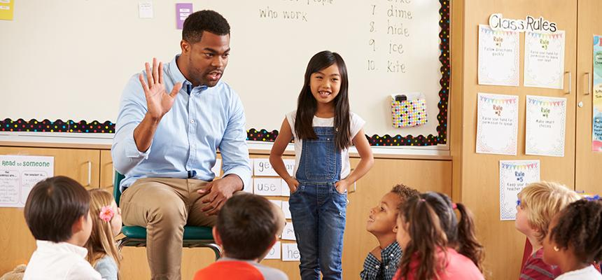 teacher holding up five fingers for students to count
