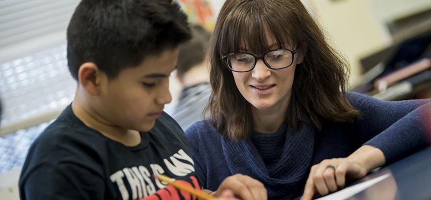 Teacher kneeling next to a student reading