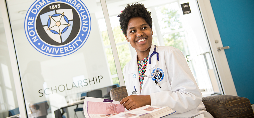 Nurse sitting at a desk with the NDMU seal in the background