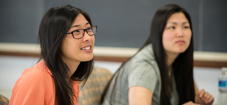 Two female students near a blackboard