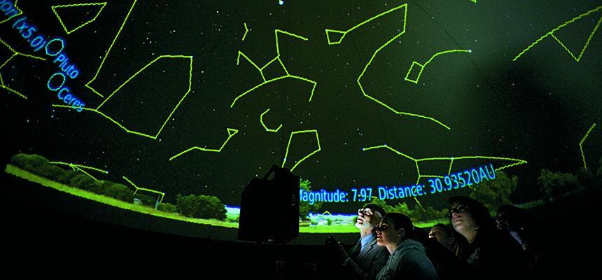 student looking at stars in planetarium